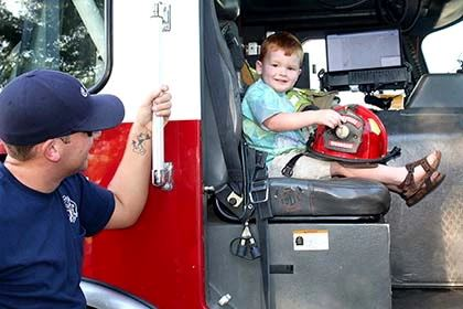 Young Boy Sitting in Fire Engine