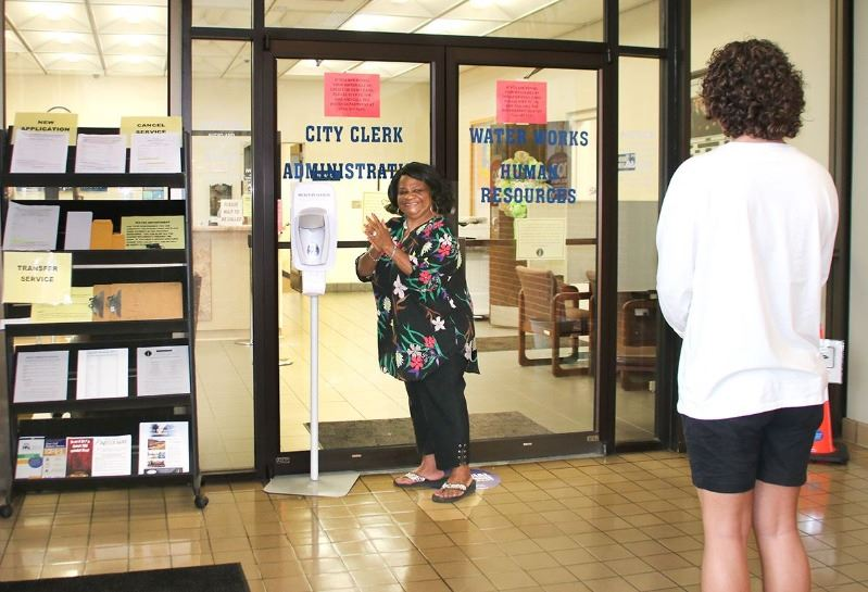 Allie Riddick sanitizes her hands at the provided hand sanitizing station outside of the City Water Department Friday. Stickers on the floor tell customers where to stand in order to maintain 6 feet of separation. Customers are also encouraged to wear masks when inside the building.